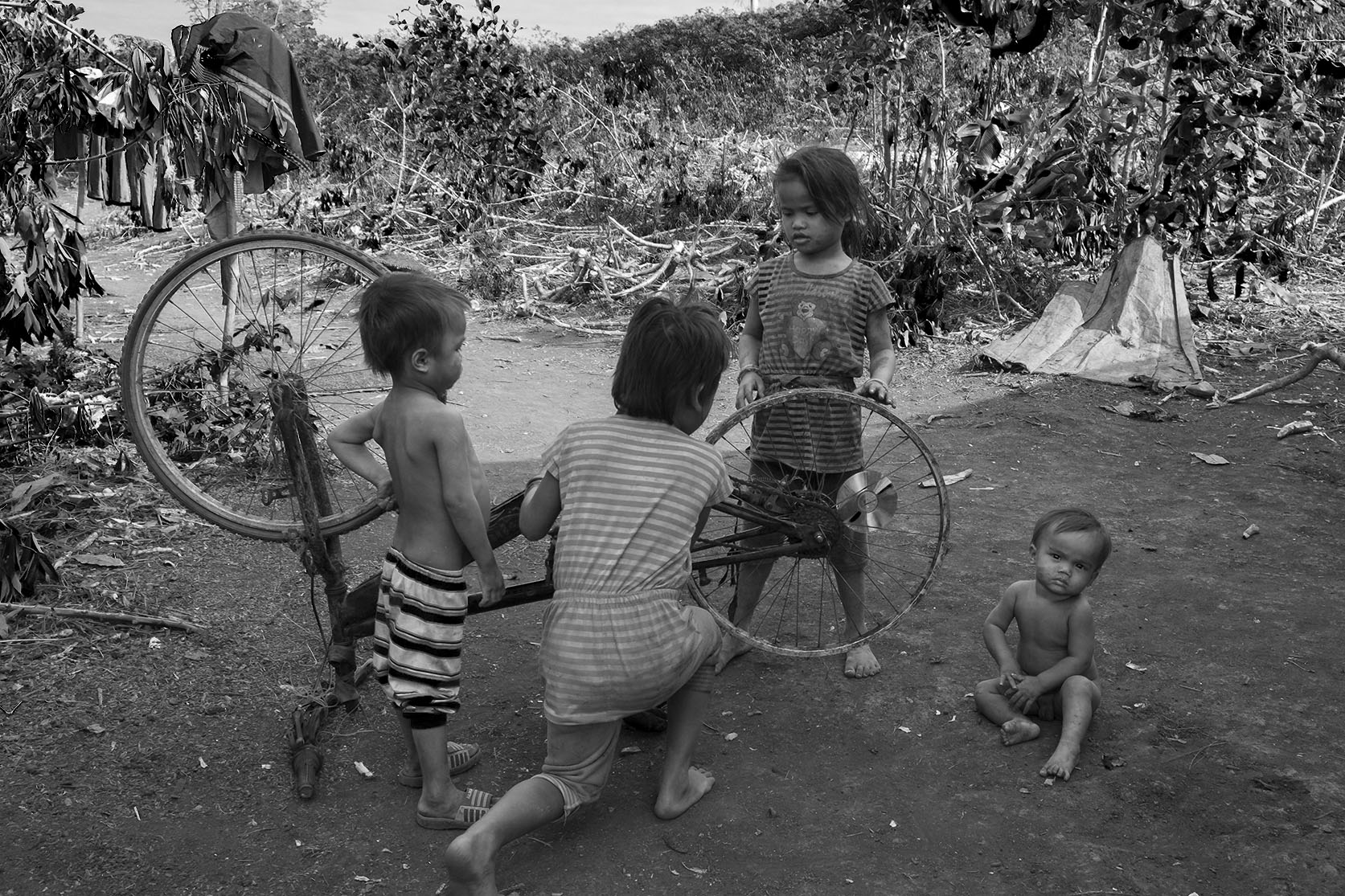 Children in ratanakiri district, Cambodia playing with an old broken bike.