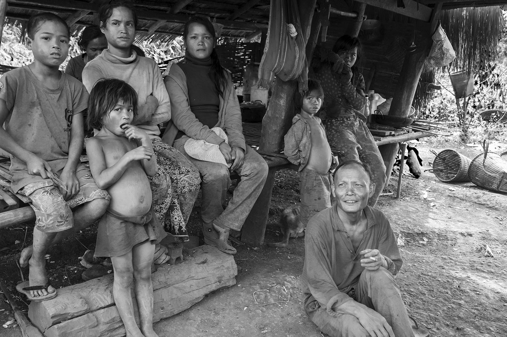 A minority family is relaxing in the shadow of their home in Ratanakiri, Cambodia