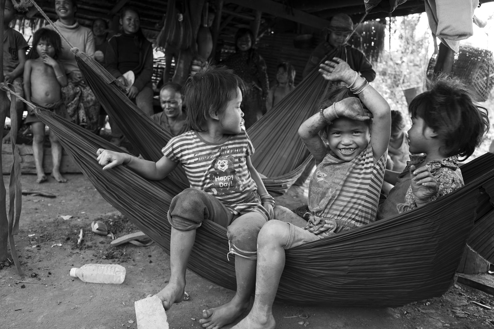 Three children sitting in a hammock under their home in ratanakiri, Cambodia