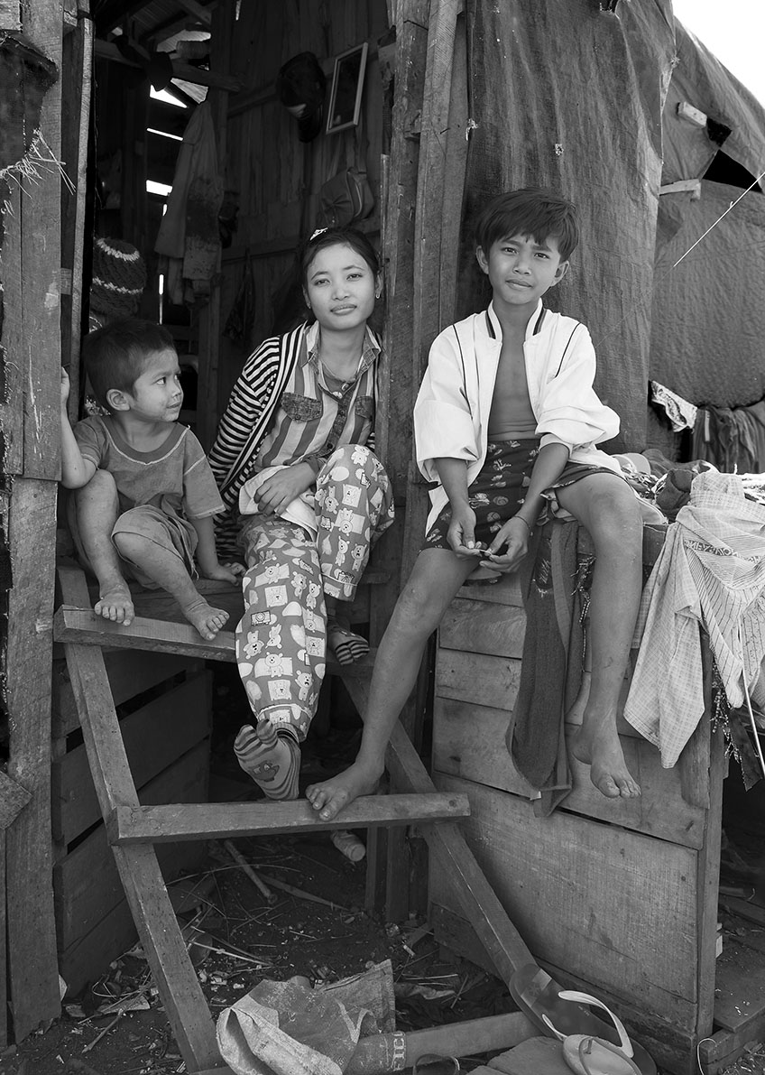 Cambodian children sitting on the doorsteps to there wooden home, a small room for the entire family