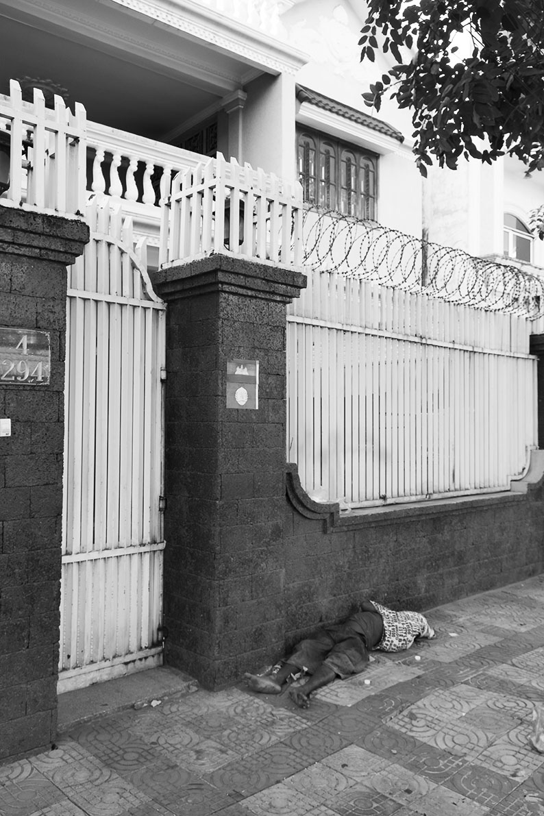 This man sleeping out on the sidewalk in Phnom Penh infront of a big luxury home, is not an uncommon scene in Cambodia.