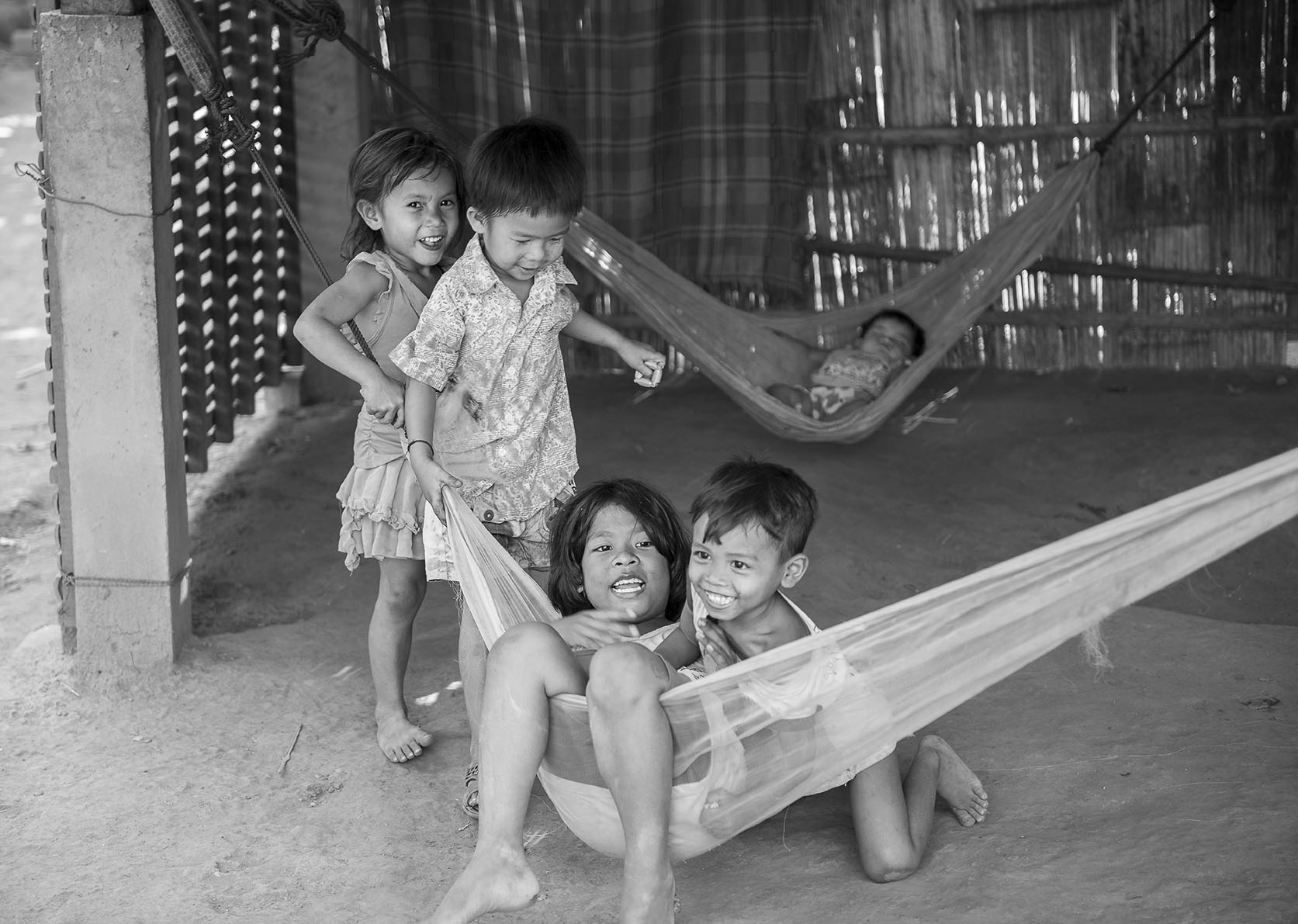 This children was playing in hammocks under their house, the family was of to work in a factory and grandmother was looking after them.